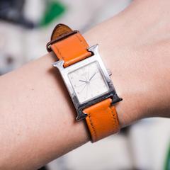 "Hermes Orange Leather & Silver Palladium ""Heure H PM"" Watch. (Photo Credit: Luxury Garage Sale Instagram Account)"